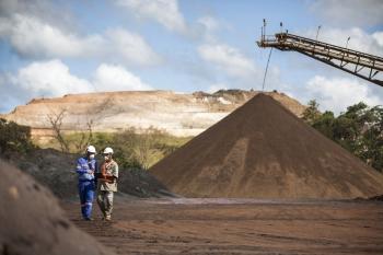 Mine workers in front of stockpile of iron ore, Amapa iron ore mine, Brazil