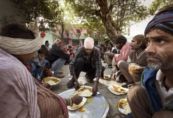 A group of homeless people at a drop-in centre in Delhi being given food, advice and help.