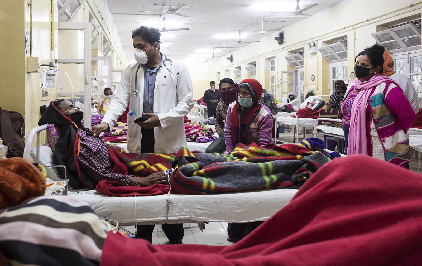 A TB patient being treated on a ward while family members look on at the National Institute of Tuberculosis and Respiratory Diseases, New Delhi.